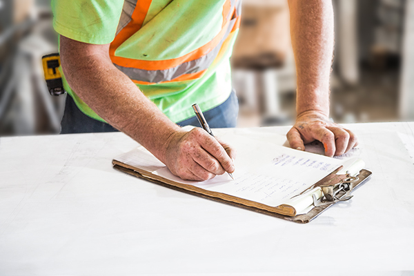 Construction  worker signing into school without a visitor management system.